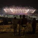 下載自美聯社 People watch from the Mangueira slum fireworks exploding above the Maracana stadium during the closing ceremony for the Summer Olympics in Rio de Janeiro, Brazil, Sunday, Aug. 21, 2016. (AP Photo/Felipe Dana)