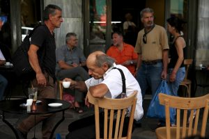 People sit outside a coffee shop in central Athens, Greece, July 20, 2015.    REUTERS/Yiannis Kourtoglou/File Photo - RTX2KVFH