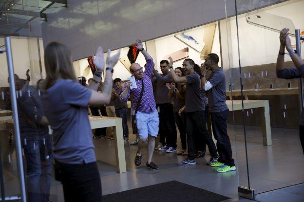 下載自路透 Jason Rappaport (C) celebrates with employees after being the first to purchase a new iPhone 6S Plus at the Apple retail store in Palo Alto, California September 25, 2015. REUTERS/Robert Galbraith - RTX1SHDR