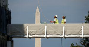 圖片來源:《達志影像》 圖片取自路透社 The Washington Monument looms in the background as construction workers look up toward the dome of the U.S. Capitol in Washington, U.S., July 8, 2016. REUTERS/Kevin Lamarque - RTX2KD9U