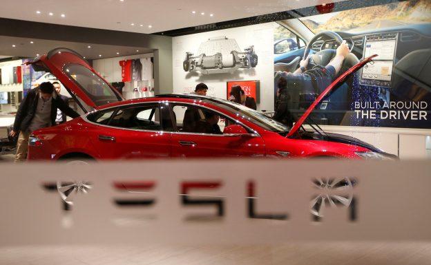 下載自路透 A man looks around Tesla Motors' Model S P85 at its showroom in Beijing January 29, 2014. REUTERS/Kim Kyung-Hoon/File Photo - RTSMACQ