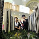圖片來源:《達志影像》 圖片取自路透社 A sales assistant (R) speaks to a customer in front of a model of a residential complex, at a real estate exhibition in Shanghai, China, April 30, 2015. Loans to Chinese property developers surged again in the first quarter despite the country's housing downturn, official data showed on April 24, a sign that authorities were exhorting banks to do more to support the cooling property market. Picture taken April 30, 2015. REUTERS/Stringer CHINA OUT. NO COMMERCIAL OR EDITORIAL SALES IN CHINA - RTX1B24H