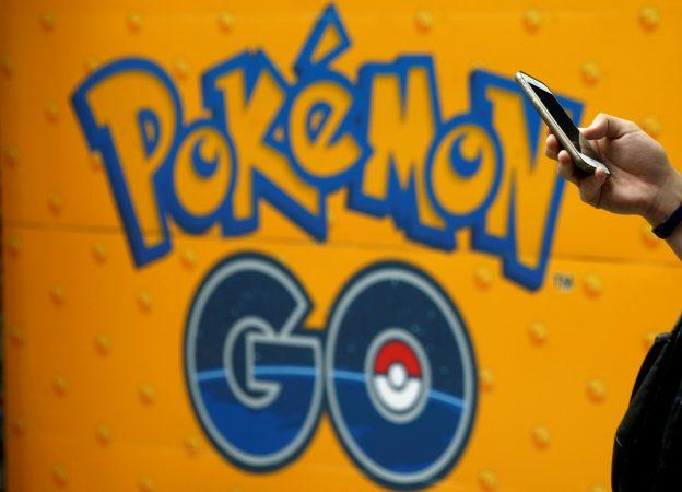 下載自路透 A man uses a mobile phone in front of an advertisement board bearing the image of Pokemon Go at an electronic shop in Tokyo, Japan, July 27, 2016.   REUTERS/Kim Kyung-Hoon/File Photo - RTX2N4E4