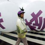 "下載自路透 A Taiwanese demonstrator walks past two balloons marked with Chinese characters reading ""Non Nuclear"" during an anti-nuclear protest in Taipei November 12, 2000. Some of 20,000 attend the demonstrstion to show their support to anti-nuclear President Chen Shui-bian. Opposition members are ganging up on Chen to bring down his government for halting construction of the island's fourth nuclear power plant, which is one-third complete.  SK/CC - RTRANUP"
