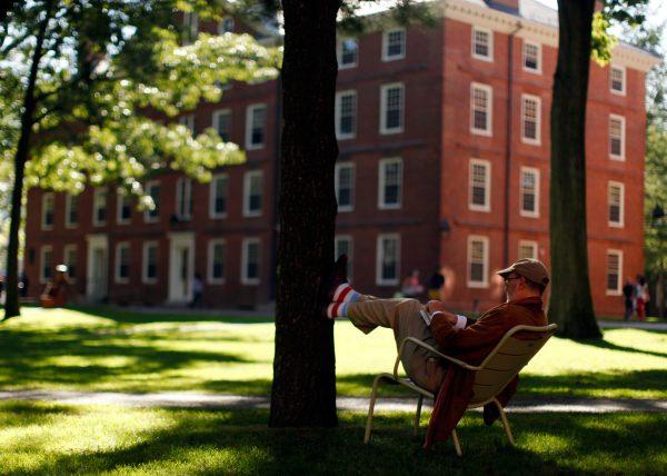 下載自路透 A man rests his feet on a tree in Harvard Yard at Harvard University in Cambridge, Massachusetts September 21, 2009. REUTERS/Brian Snyder (UNITED STATES) For best quality see GM1E6450PAG01. - RTR285OO