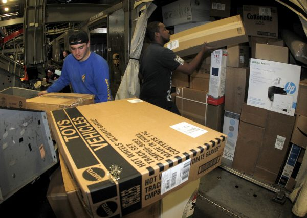 下載自路透 United Parcel Service employees load packages into containers at the UPS Worldport All Points International Hub during the peak delivery month in Louisville, Kentucky December 3, 2015. UPS expects to deliver more than 36 million air and ground packages globally on their peak day December 22. This year, UPS expects to deliver more than 630 million packages globally during the time between Thanksgiving and Christmas. Picture taken on December 3, 2015. REUTERS/John Sommers II - RTX1X7US