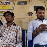 下載自路透 Commuters watch videos on their mobile phones as they travel in a suburban train in Mumbai, India, April 2, 2016. With smartphone sales booming and India preparing for nationwide 4G Internet access, India's film and TV industry hopes the ease of tapping your phone for the latest release will generate profits at last, overcoming the problems of woefully few cinemas and rampant piracy. Picture taken April 2, 2016. REUTERS/Shailesh Andrade - RTSDS09