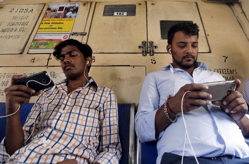 下載自路透 Commuters watch videos on their mobile phones as they travel in a suburban train in Mumbai, India, April 2, 2016. With smartphone sales booming and India preparing for nationwide 4G Internet access, India