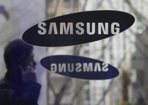 下載自美聯社 FILE - In this Dec. 12, 2013 file photo, a man passes by the Samsung Electronics Co. logos at its headquarters in Seoul, South Korea. In a patent fight with Apple, Samsung is asking the Supreme Court to take a digital-age look at a type of dispute it last confronted in the horse-and-buggy era. South Korea-based Samsung on Monday appealed a $399 million judgment for illegally copying patented aspects of the look of Apple's iPhone, the latest round in a long-running fight between the two tech industry giants. (AP Photo/Ahn Young-joon, File)