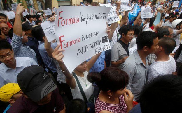 下載自路透 Demonstrators, holding signs to protest against Taiwanese enterprise Formosa Plastic and environmental-friendly messages, say they are demanding cleaner waters in the central regions after mass fish deaths in recent weeks, in Hanoi, Vietnam May 1, 2016. REUTERS/Kham - RTX2CA02