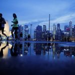 下載自路透 Joggers run past as the skyline of Singapore's financial district is seen in the background April 21, 2014. REUTERS/Edgar Su/File Photo - RTX2N0SC