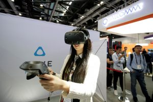A participant wearing a virtual reality headset HTC VIVE plays a game at the Global Mobile Internet Conference (GMIC) 2016 in Beijing, China, April 28, 2016. REUTERS/Jason Lee   - RTX2C0GW