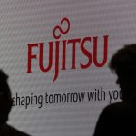 People are silhouetted against a screen displaying a logo of Fujitsu at CEATEC JAPAN 2012 electronics show in Chiba, east of Tokyo, October 2, 2012. Japan's largest cutting-edge IT and electronics trade show started on Tuesday and runs until October 6 at Makuhari Messe convention center. REUTERS/Yuriko Nakao (JAPAN - Tags: BUSINESS) - RTR38OVD