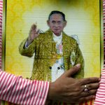 A well-wisher hugs a portrait of Thailand's King Bhumibol Adulyadej at the Siriraj hospital where he is residing in Bangkok, Thailand, October 13, 2016. REUTERS/Chaiwat Subprasom - RTSS1UA