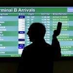 下載自美聯社 FILE - In this Wednesday, Nov. 27, 2013, file photo, a person points to a screen with an airplane travel list while holding up a phone at Newark Liberty International Airport, in Newark, N.J. Some airlines are taking extra steps to prevent a disaster in case a passenger's device powered by a lithium ion battery catches fire during flight. At least three U.S. airlines are adding new fire-suppression equipment to fleets in case a cellphone or laptop battery overheats, catches on fire and can't be extinguished. (AP Photo/Julio Cortez, File)
