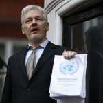 下載自路透 WikiLeaks founder Julian Assange holds a copy of a U.N. ruling as he makes a speech from the balcony of the Ecuadorian Embassy, in central London, Britain February 5, 2016. Assange should be allowed to go free from the Ecuadorian embassy in London and be awarded compensation for what amounts to a three-and-a-half-year arbitrary detention, a U.N. panel ruled on Friday.       REUTERS/Peter Nicholls  - RTX25MJM