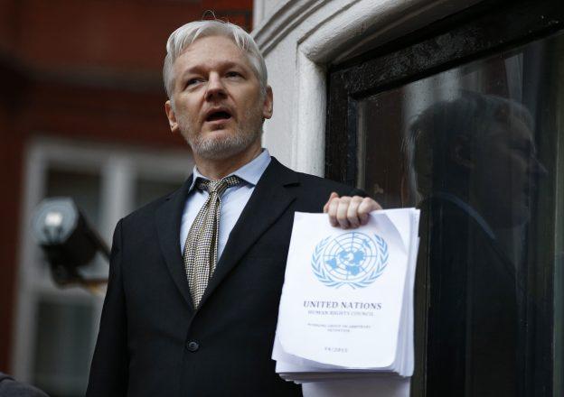 下載自路透 WikiLeaks founder Julian Assange holds a copy of a U.N. ruling as he makes a speech from the balcony of the Ecuadorian Embassy, in central London, Britain February 5, 2016. Assange should be allowed to go free from the Ecuadorian embassy in London and be awarded compensation for what amounts to a three-and-a-half-year arbitrary detention, a U.N. panel ruled on Friday.       REUTERS/Peter Nicholls  - RTX25MJM