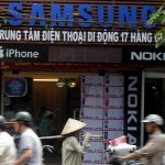 People pass a shop selling mobile phones by Samsung, Nokia and Apple in Hanoi April 13, 2012. Samsung Electronics Co Ltd will overtake Nokia Oyj as the No 1 cellphone manufacturer in a slowing global handset market, a Reuters poll of banks, brokerages and research firms showed on Thursday. REUTERS/Kham (VIETNAM - Tags: BUSINESS SCIENCE TECHNOLOGY TELECOMS) - RTR30OMC
