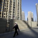 圖片來源:《達志影像》 圖片取自路透社 A woman walks past a residential compound in Beijing's Tongzhou district, China, February 25, 2016. China's home prices rose for a fourth straight month in January with big cities leading the gains, suggesting an uneven recovery in the housing market as the government's pro-growth policies gain traction. REUTERS/Jason Lee - RTX28NEV