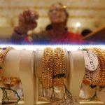 圖片來源:《達志影像》 圖片取自路透社 Gold bangles are on display as a woman makes choices at a jewellery showroom during Dhanteras, a Hindu festival associated with Lakshmi, the goddess of wealth, in Kolkata, India October 28, 2016. REUTERS/Rupak De Chowdhuri  - RTX2QUHN