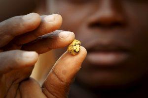 下載自路透 A gold prospector holds a gold nugget between his fingers at a gold mine near the village of Gamina in western Ivory Coast, March 16, 2015. Picture taken March 16, 2015.    To match Special Report IVORYCOAST-GOLD/ARMY   REUTERS/Luc Gnago - RTX1BX78