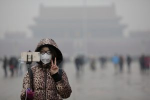 "A woman wearing a protective mask has her picture taken just after a flag-raising ceremony amid heavy smog at the Tiananmen Square, after the city issued its first ever ""red alert"" for air pollution, in Beijing December 9, 2015.   REUTERS/Damir Sagolj - RTX1XTUO"