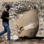下載自路透 A man passes by what appears to be the head of an unearthed statue that workers say depicts Pharaoh Ramses II, in Cairo, Egypt, March 9, 2017. REUTERS/Mohamed Abd El Ghany - RTS125VR