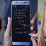 下載自路透 A man uses his mobile phone next to advertisements promoting Samsung Electronics' Galaxy Note 7 at the company's headquarters in Seoul, South Korea, October 10, 2016.   REUTERS/Kim Hong-Ji - RTSRK3X