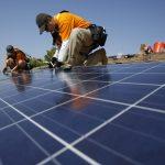 下載自路透 Vivint Solar technicians install solar panels on the roof of a house in Mission Viejo, California October 25, 2013.  REUTERS/Mario Anzuoni  (UNITED STATES - Tags: ENERGY) - RTX14U4H