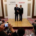 下載自路透 Honda Chief Executive Officer Takahiro Hachigo (R) and his Hitachi Automotive counterpart Hideaki Seki shake hands at a photo session after their news conference in Tokyo, Japan, February 7, 2017.  REUTERS/Kim Kyung-Hoon - RTX2ZYMY
