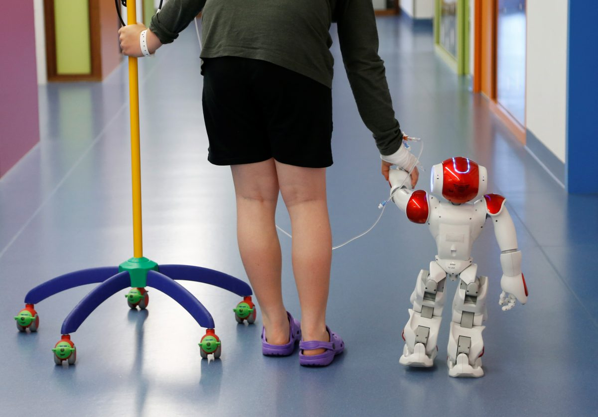 "下載自路透社 Belgian Ian Frejean, 11, walks with ""Zora"" the robot, a humanoid robot designed to entertain patients and to support care providers, at AZ Damiaan hospital in Ostend, Belgium June 16, 2016. REUTERS/Francois Lenoir  - RTX2GKOB"