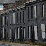 下載自路透 A man walks his dog past a row of boarded up terraced houses in Liverpool, northern England September 2, 2013. A new, government backed, scheme called The National Empty Home Loans Fund has been launched aimed at repairing some of England's 710,000 empty houses and returning them to residential use at affordable rents according to local media. REUTERS/Phil Noble (BRITAIN - Tags: BUSINESS CONSTRUCTION POLITICS REAL ESTATE) - RTX134O1