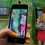 """下載自路透 A woman plays the augmented reality mobile game """"Pokemon Go"""" by Nintendo, as a visitor uses an automated teller machine (ATM) at a branch of Sberbank in central Krasnoyarsk, Siberia, Russia, July 20, 2016. REUTERS/Ilya Naymushin - RTSIVYJ"""