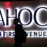 下載自美聯社 FILE - In this Nov. 5, 2014, file photo, a person walks in front of a Yahoo sign at the company's headquarters in Sunnyvale, Calif. Verizon bought Yahoo in a sale announced Monday, July 25, 2016. (AP Photo/Marcio Jose Sanchez, File)