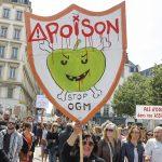 """下載自路透 A woman holds a placard, """"Poison - Stop GMO"""" as more than one thousand people participate in a protest march against Monsanto, the world's largest seed company, in Lyon, France, May 23, 2015. People in 48 countries and 421 cities will take part in protest marches against Monsanto and its glyphosate-containing Roundup herbicide.  REUTERS/Emmanuel Foudrot   - RTX1E8PK"""