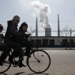 Two young children ride a bicycle with their mother past abandoned buildings in front of a chimney billowing smoke from a nearby coal-burning power station in Beijing March 10, 2010. China signed up, along with India, to the Copenhagen Accord for fighting climate change on Tuesday, joining almost all other major greenhouse gas emitters in endorsing the non-binding pact.     REUTERS/David Gray      (CHINA - Tags: ENVIRONMENT POLITICS ENERGY BUSINESS) - RTR2BG28