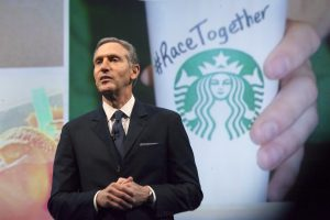 "下載自路透 Starbucks Corp Chief Executive Howard Schultz, pictured with images from the company's new ""Race Together"" project behind him, speaks during the company's annual shareholder's meeting in Seattle, Washington March 18, 2015. Schultz has deftly navigated thorny issues such as gay marriage, gun control and Congressional gridlock, but his move to weigh in on U.S. race relations has brewed up a social media backlash. The company kicked off the discussion when it published full-page ads in major U.S. newspapers earlier this week with the words ""Shall We Overcome?"" at center page and ""RaceTogether"" and the Starbucks logo near the bottom.  REUTERS/David Ryder  (UNITED STATES - Tags: BUSINESS) - RTR4TXN7"