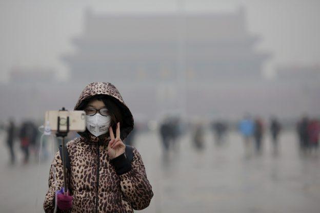 """下載自路透 A woman wearing a protective mask has her picture taken just after a flag-raising ceremony amid heavy smog at the Tiananmen Square, after the city issued its first ever """"red alert"""" for air pollution, in Beijing December 9, 2015.   REUTERS/Damir Sagolj - RTX1XTUO"""